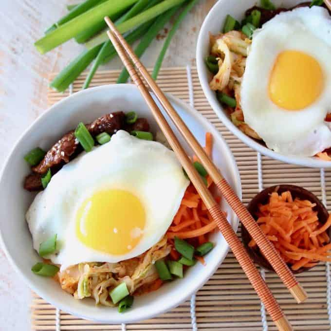 Cauliflower rice bowls topped with fried eggs and shredded carrots