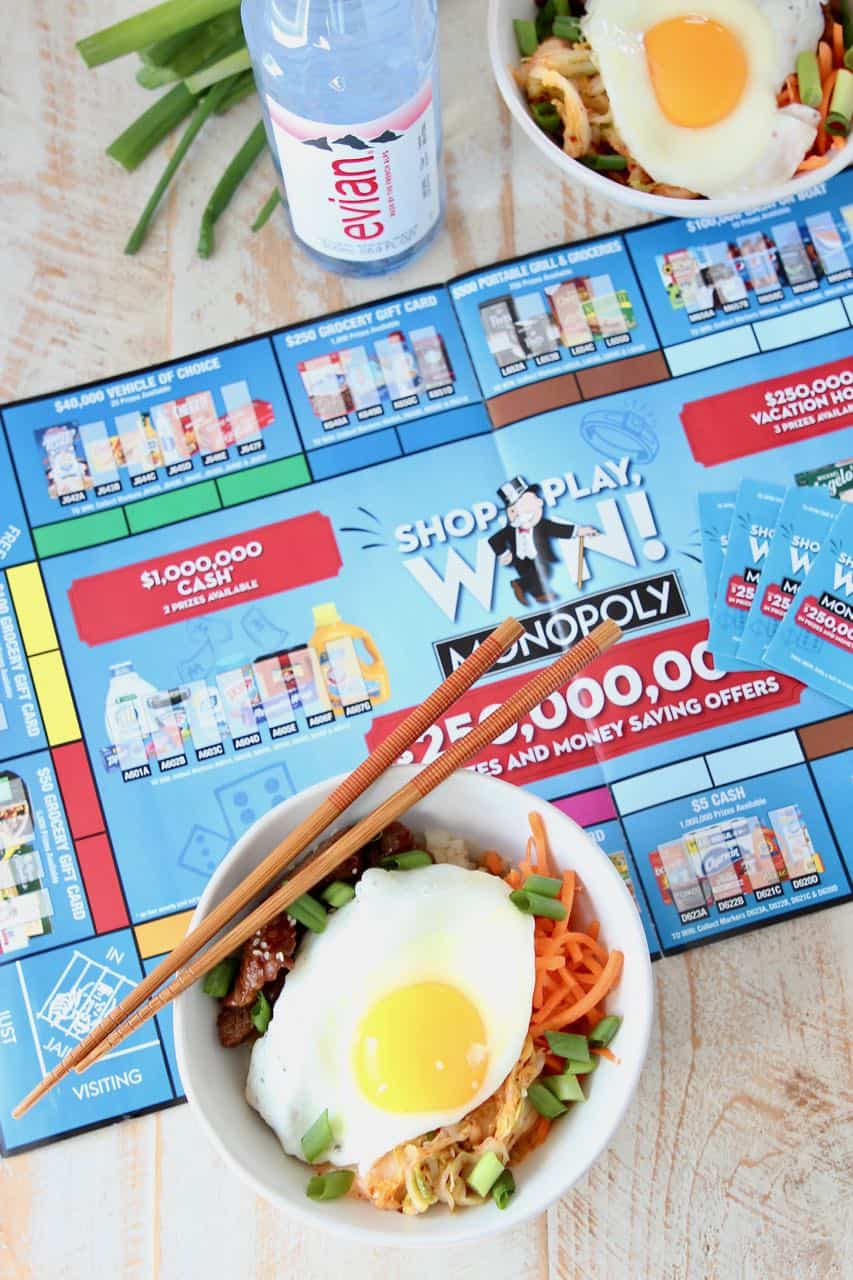 Korean BBQ rice bowls topped with fried egg sitting on Albertsons Monopoly board