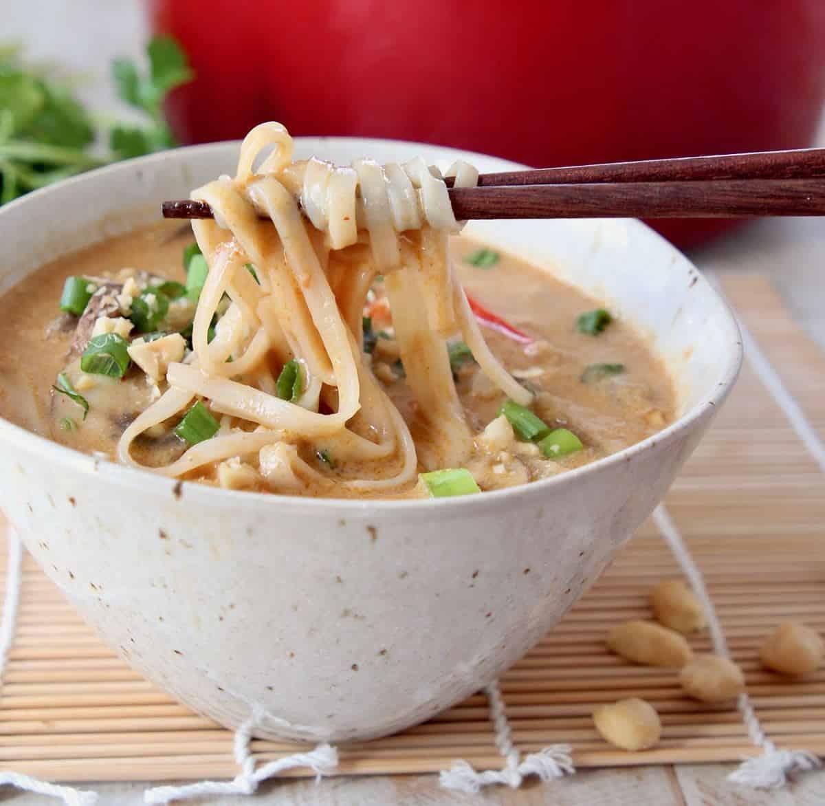 Chopsticks pulling noodles out of a bowl of soup