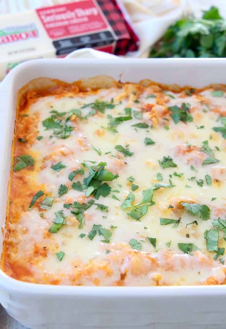 Cheesy cauliflower casserole in baking dish, topped with fresh cilantro