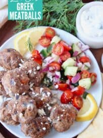 overhead image of greek meatballs stacked up on plate next to tomato cucumber salad