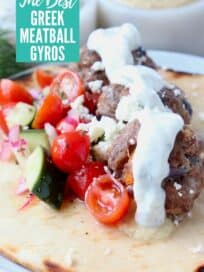 greek meatball gyro on plate topped with tzatziki sauce