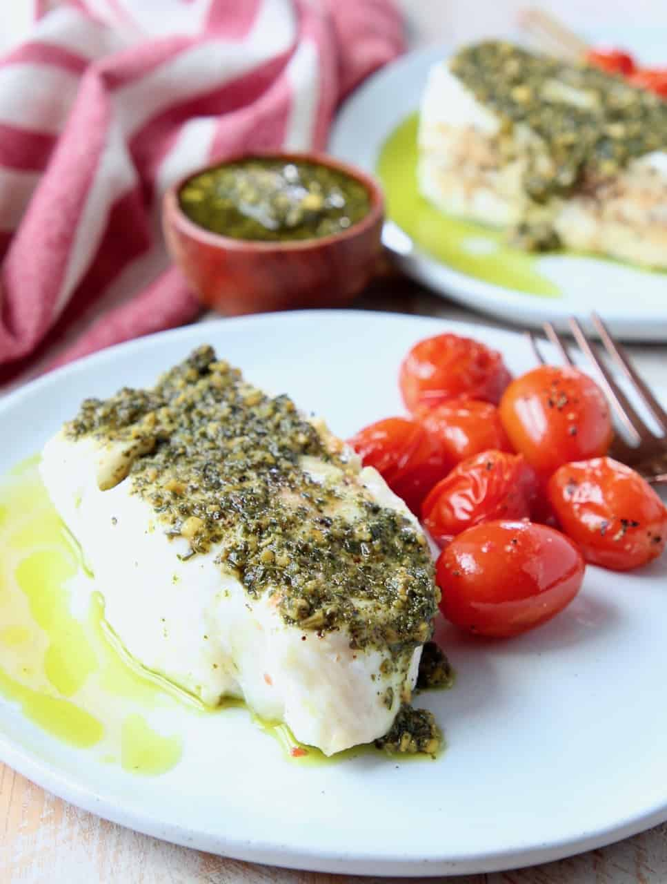 Sea bass topped with pesto on plate with cherry tomatoes