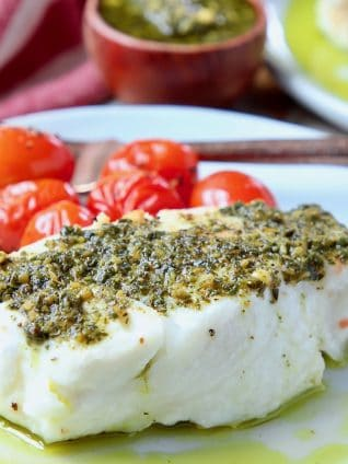 Sea bass covered in pesto on plate with cherry tomatoes