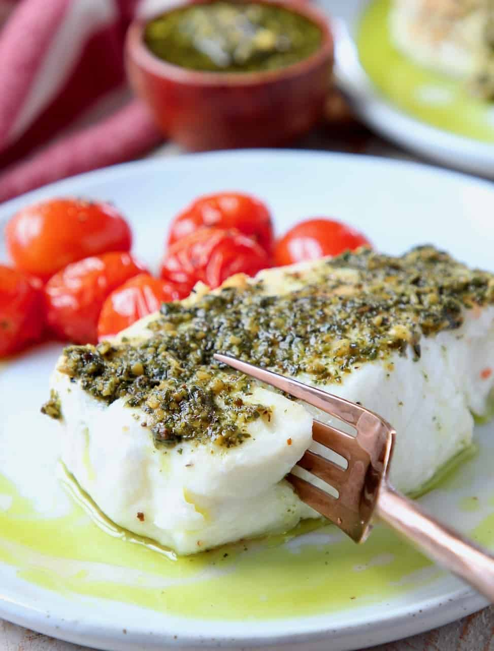 Fork cutting into sea bass on plate, topped with pesto
