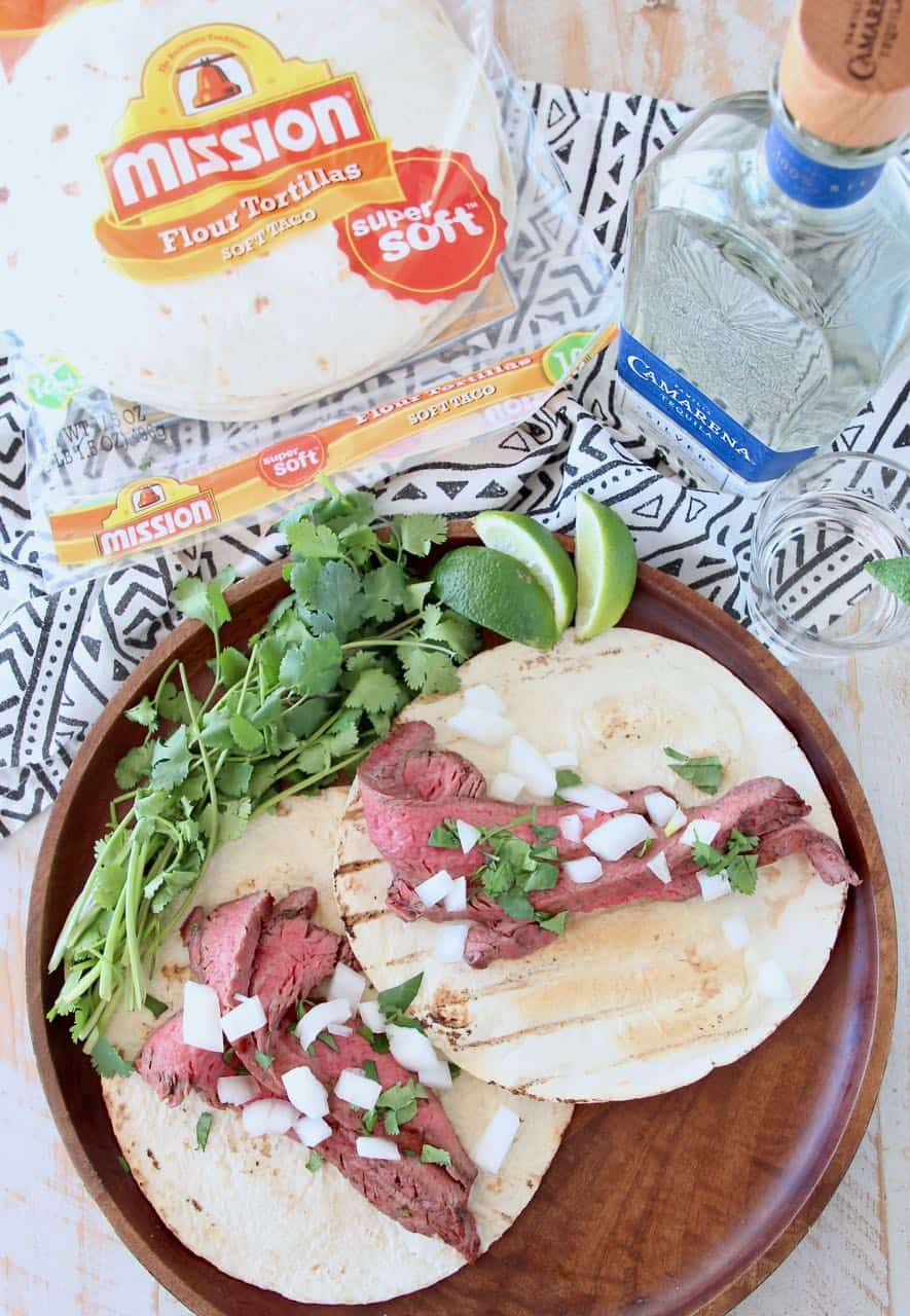 Carne asada tacos on wood tray with fresh cilantro