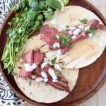Two carne asada tacos on wood tray with fresh cilantro sprigs