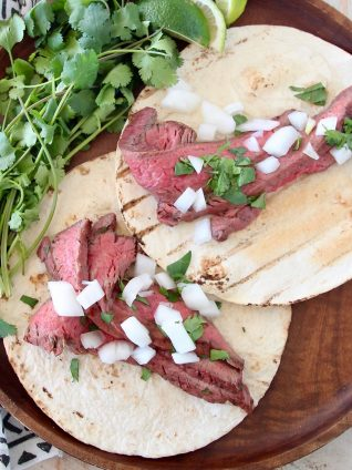 Two carne asada tacos on wood tray with fresh cilantro sprigs