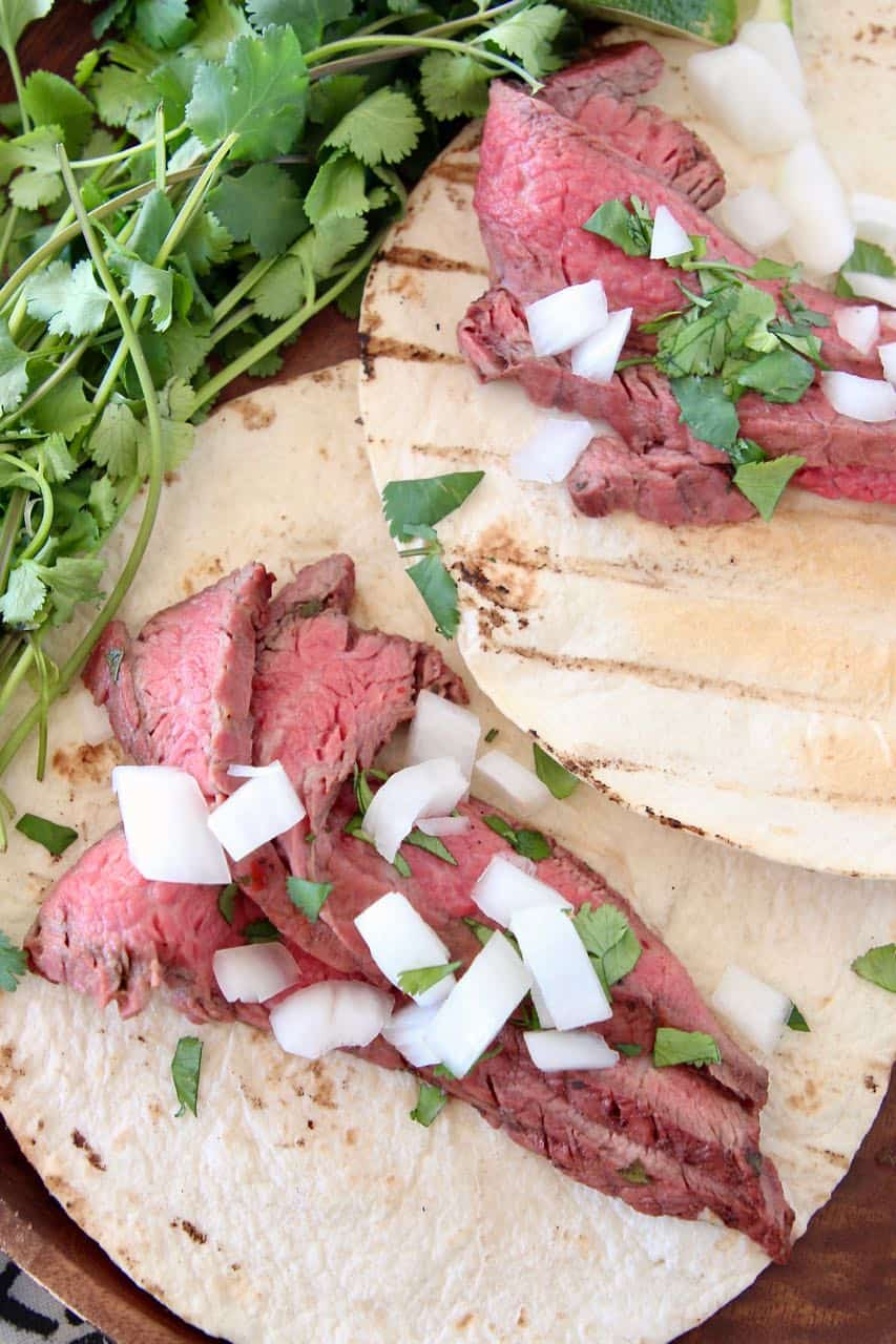 Sliced carne asada in tortillas topped with diced onions and cilantro