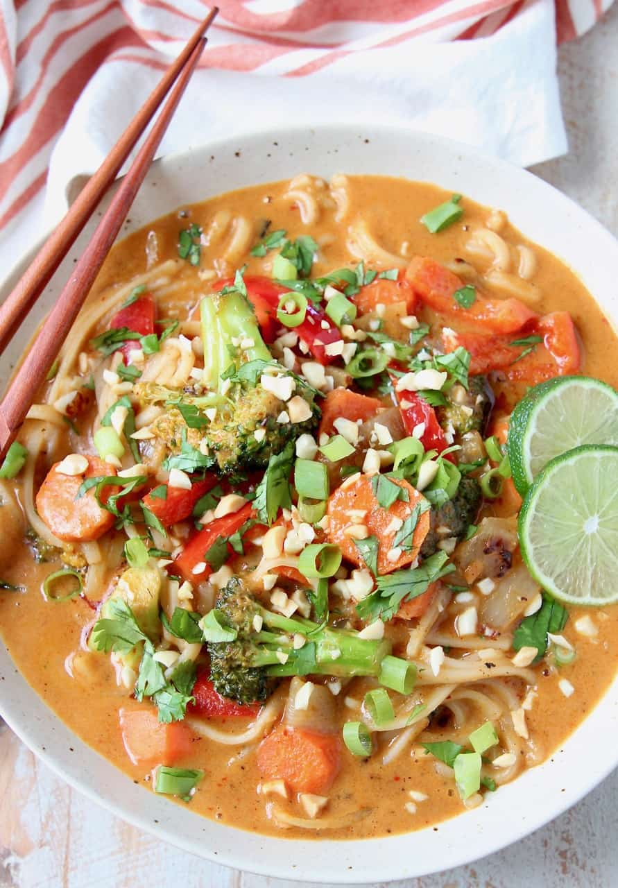 Overhead image of vegetable massaman curry in bowls with noodles and lime wedges