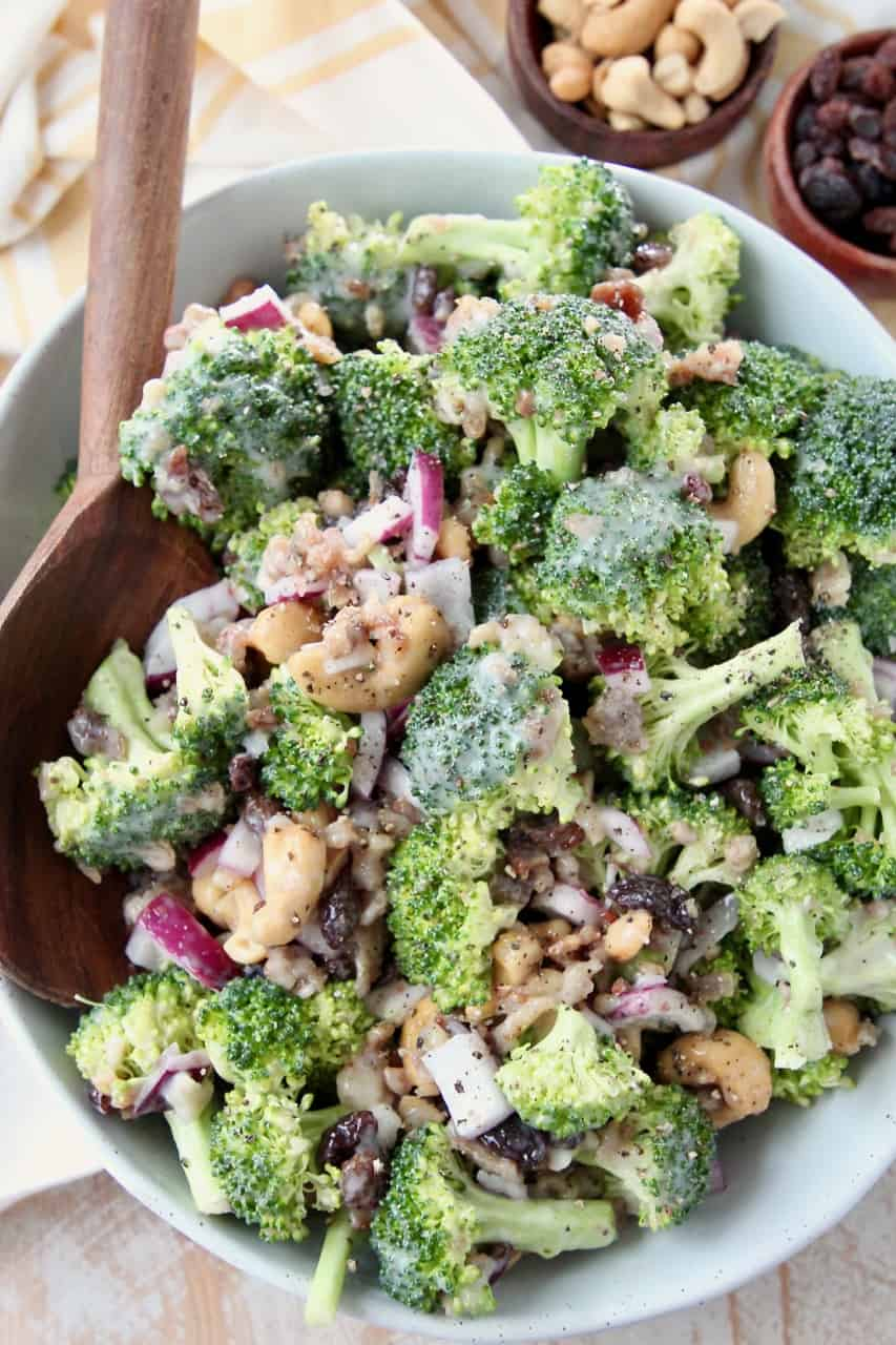 Broccoli salad in bowl with large wooden serving spoon