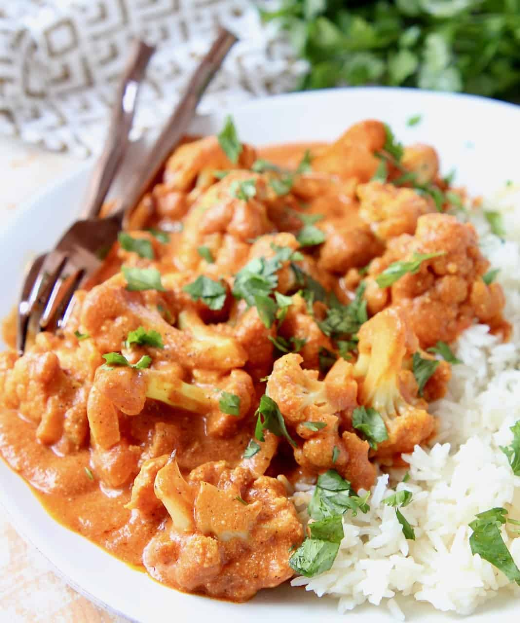 Cauliflower florets on plate covered in curry sauce