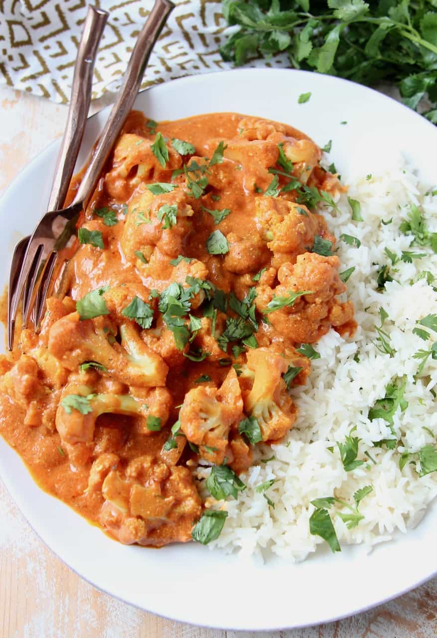 Cauliflower covered in curry sauce on plate with rice and forks