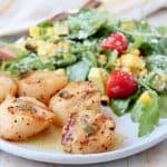 Grilled scallops on plate with arugula salad