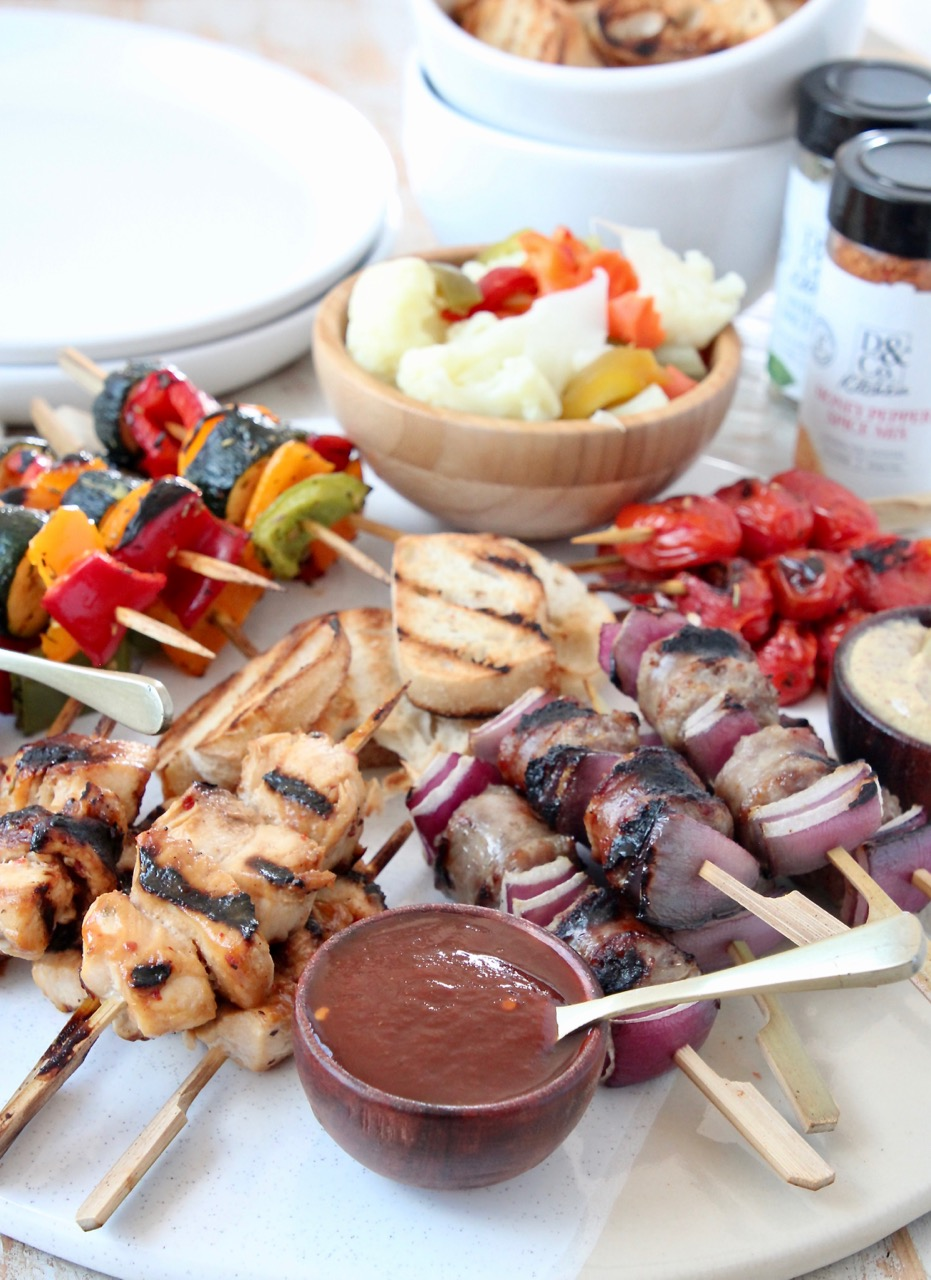 Grilled mini skewers on charcuterie board with bowls of sauces