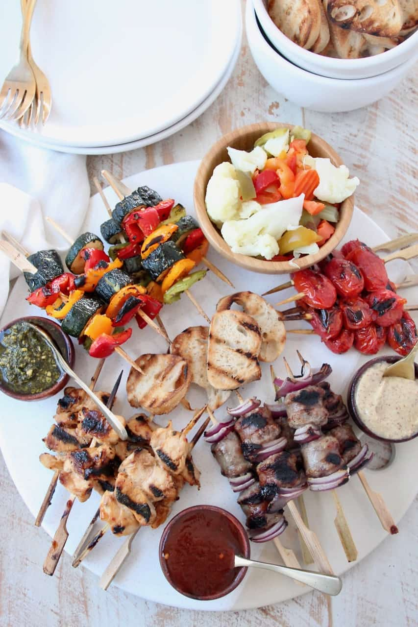 Overhead image of grilled mini skewers on charcuterie board with small bowls of sauces