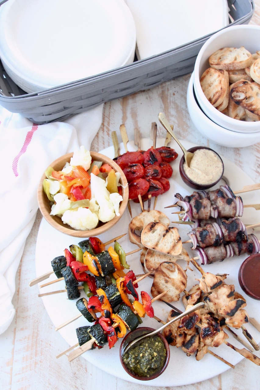 Grilled mini skewers on charcuterie board next to bowl of toasted baguette slices and basket of napkins