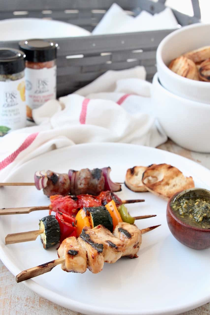 Grilled skewers on plate with small bowl of pesto and grilled slices of bread