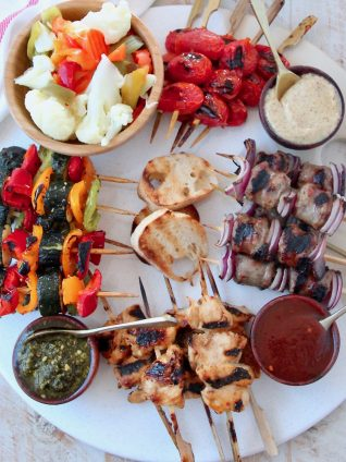 Overhead image of grilled skewers on charcuterie platter