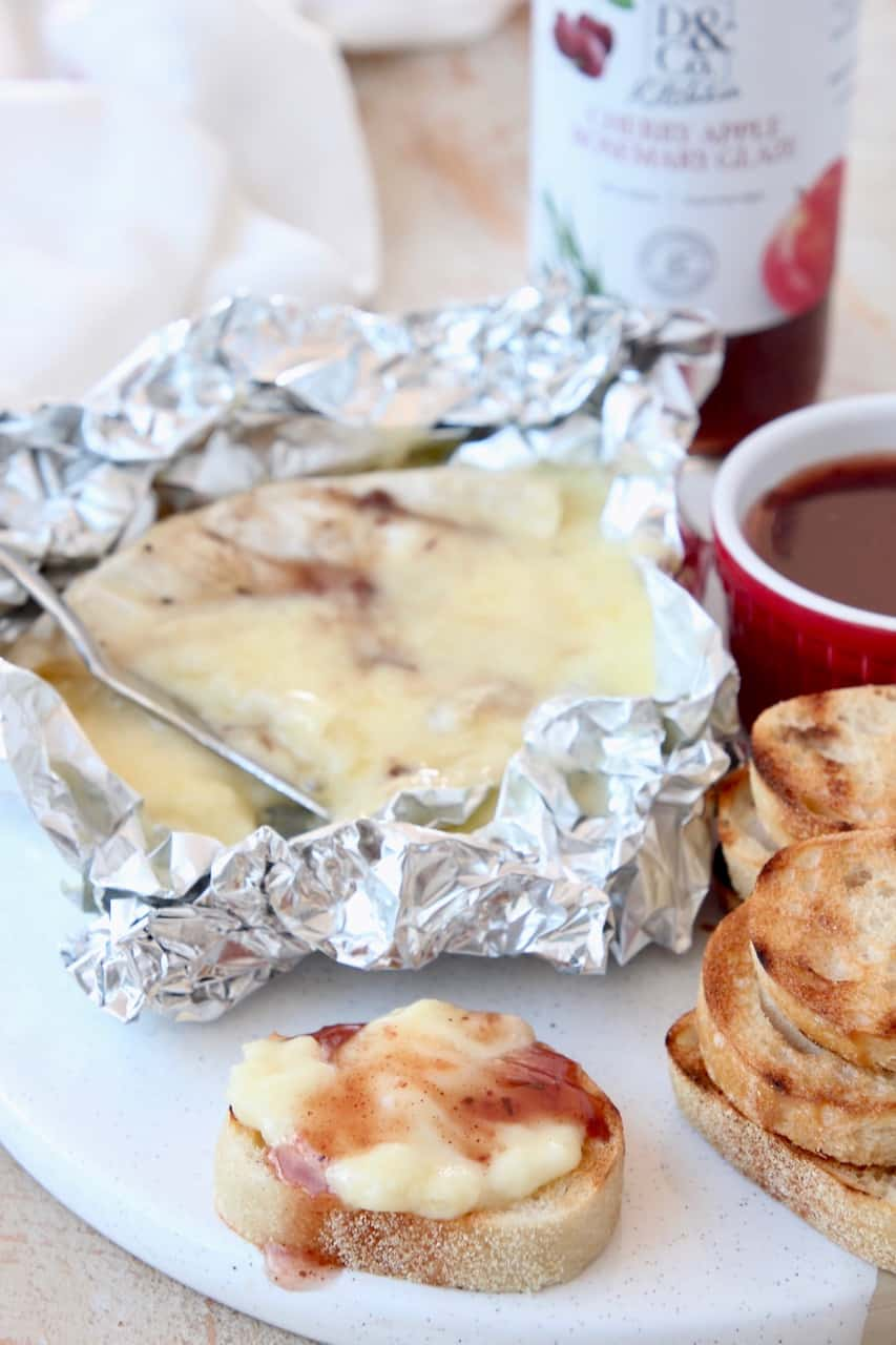 Melted grilled brie in piece of foil with baguette slices