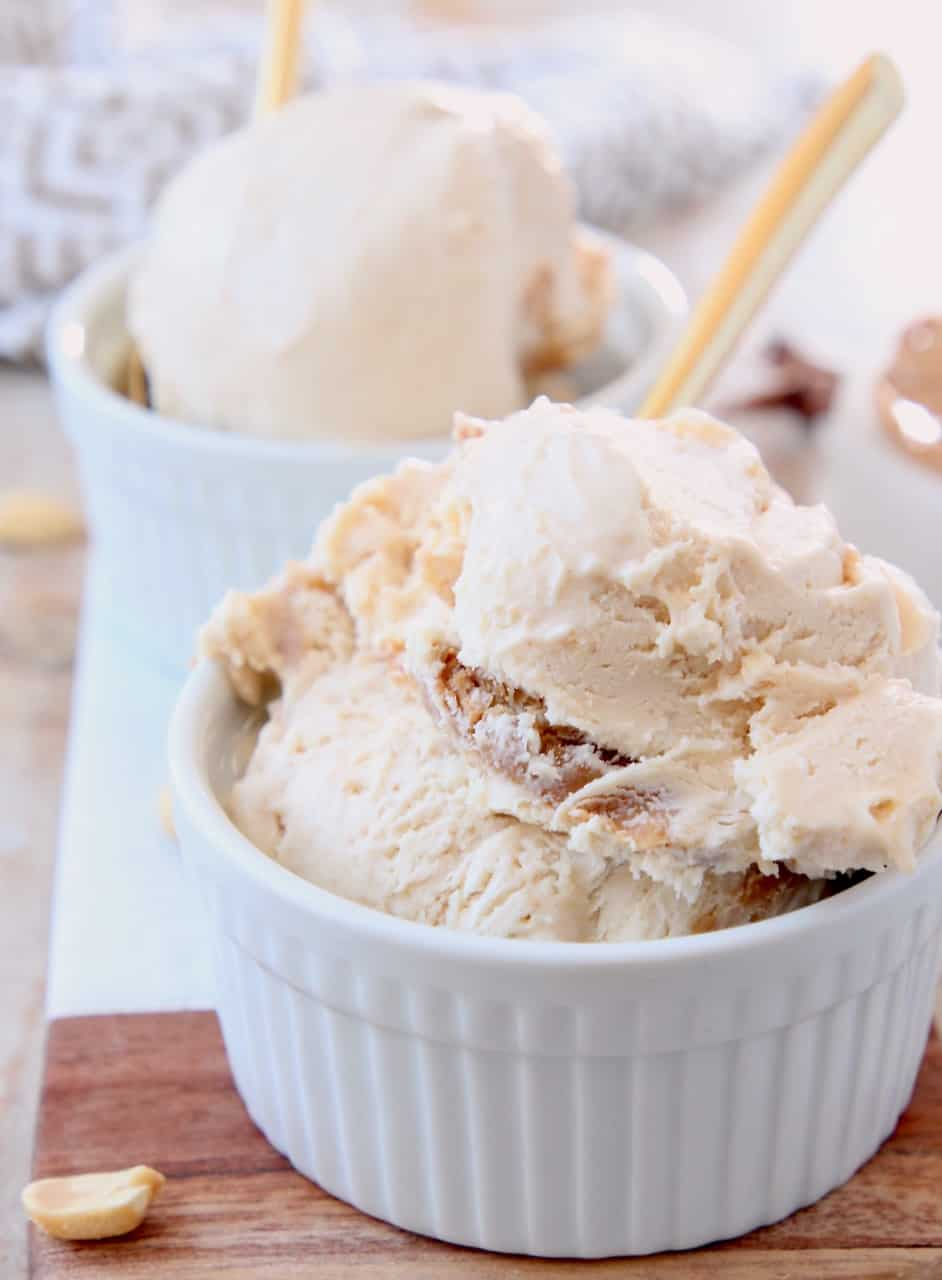 Scoops of peanut butter ice cream in small white bowl with gold spoon