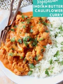 Cauliflower covered in curry sauce on plate with rice and cilantro