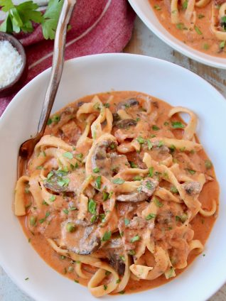 Overhead image of pasta in mushroom sauce in bowl with fork