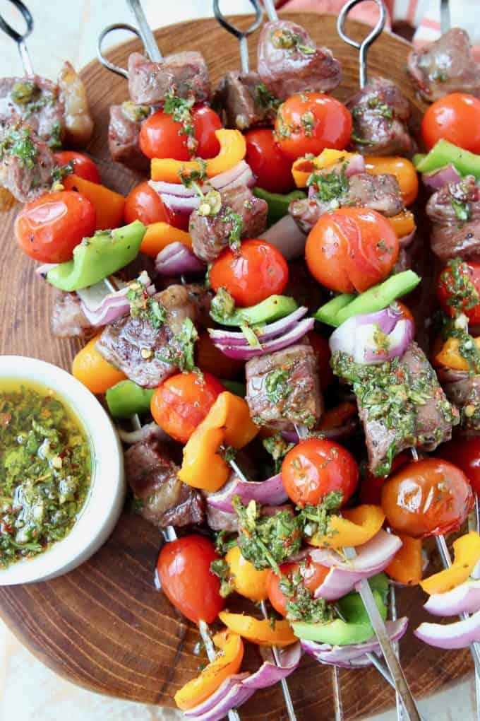 Grilled steak and vegetable skewers on wood cutting board