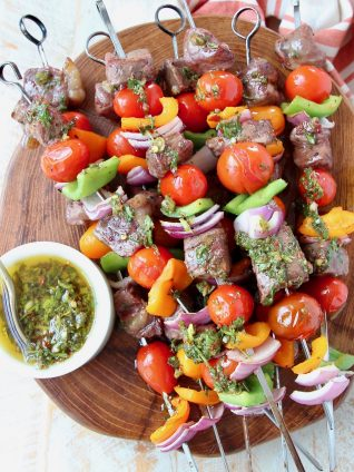 Steak kabobs stacked up on wood cutting board with chimichurri sauce in bowl on the side