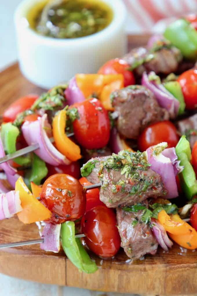 Steak kabobs with veggies on wood board