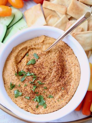 Spicy hummus in bowl topped with chopped cilantro and paprika