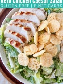 Sliced chicken on top of caesar salad