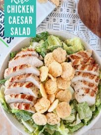 Sliced grilled chicken on caesar salad in bowl