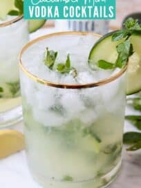 Cocktail in gold rimmed glass with mint and cucumber