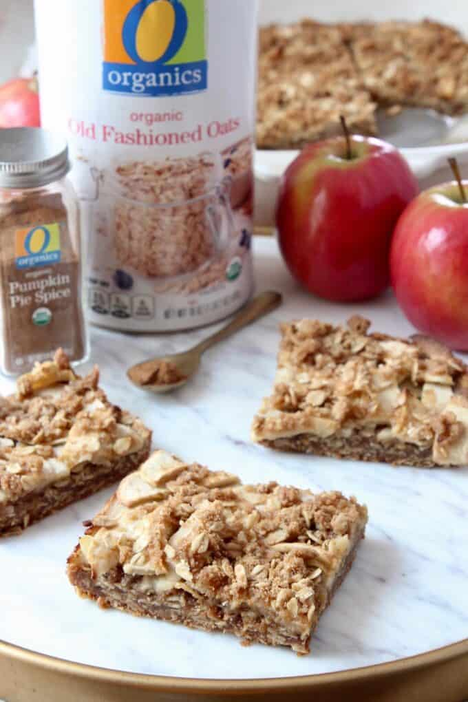 apple oatmeal bars on marble serving tray with apples