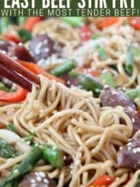 chopsticks swirling noodles in skillet of stir fry