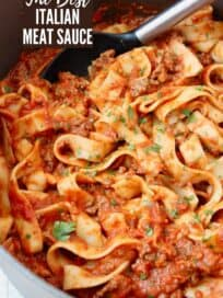 Pasta tossed in meat sauce in large pot with serving spoon in the pot