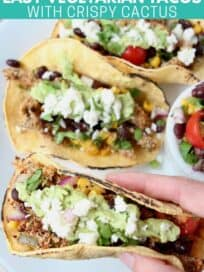 Hand holding taco over plate of tacos
