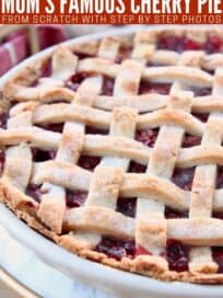cherry pie with lattice crust in pie plate on marble serving tray