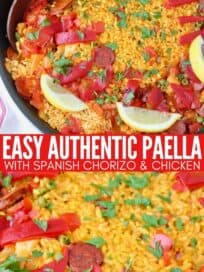 spanish paella in skillet topped with lemon wedges