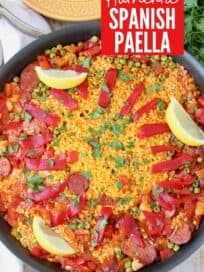 Overhead image of paella in skillet topped with sliced peppers and lemon wedges