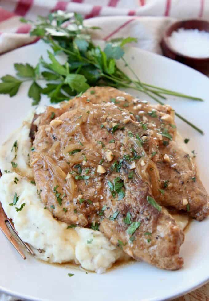pork chops stacked up on plate on top of mashed potatoes
