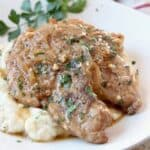two pork chops on plate covered with gravy, on top of mashed potatoes