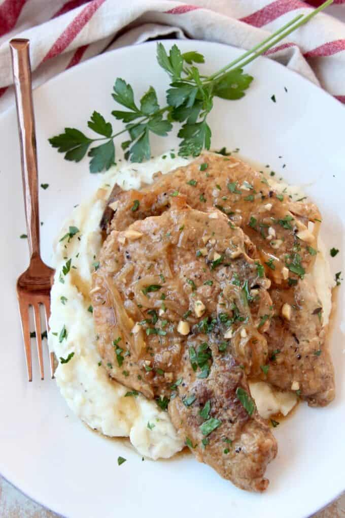 Overhead image of two pork chops on plate with mashed potatoes and brown gravy