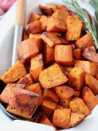 roasted cubed sweet potatoes in bowl with serving spoon and rosemary sprigs
