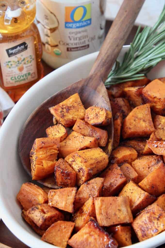 honey roasted cubed sweet potatoes in bowl with wooden serving spoon