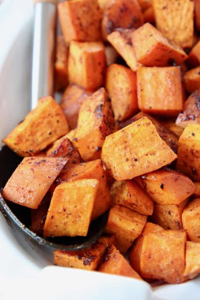 Roasted cubed sweet potatoes in bowl with serving spoon