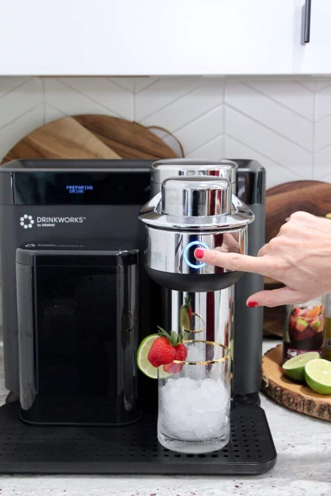 finger pressing start button on drinkworks machine