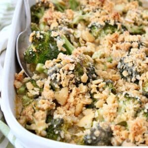 broccoli casserole with ritz cracker topping in dish with serving spoon