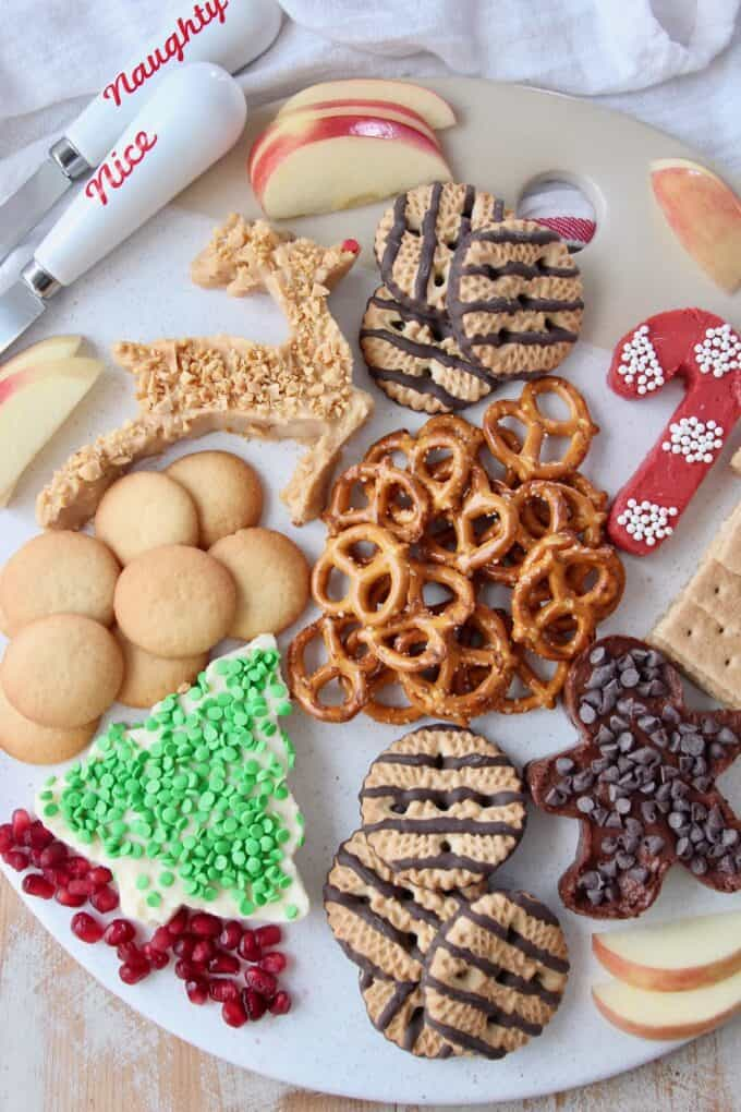 overhead image of dessert board with pretzels, cookies and cream cheese dip in holiday shapes